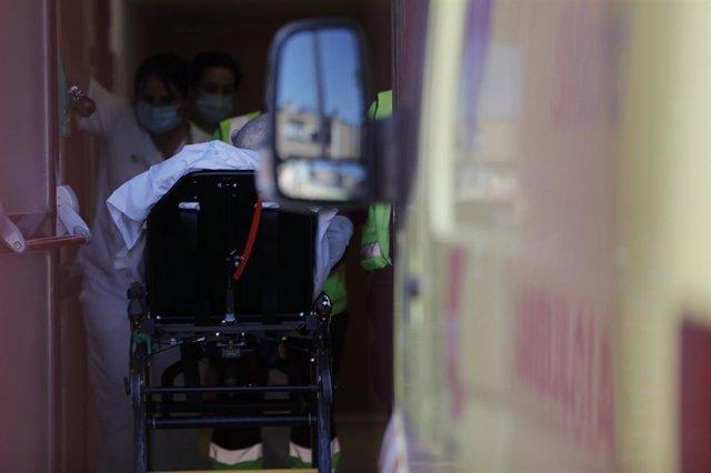 Personal sanitario ante una ambulancia con un paciente, en una imagen de archivo.