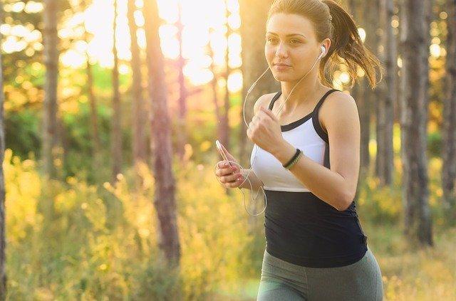 Mujer haciendo deporte mientras escucha música con unos auriculares, running, correr, carrera.