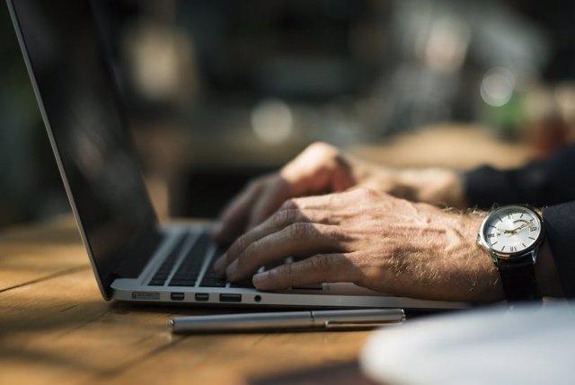 Imatge d'un treballador amb un ordinador portàtil.