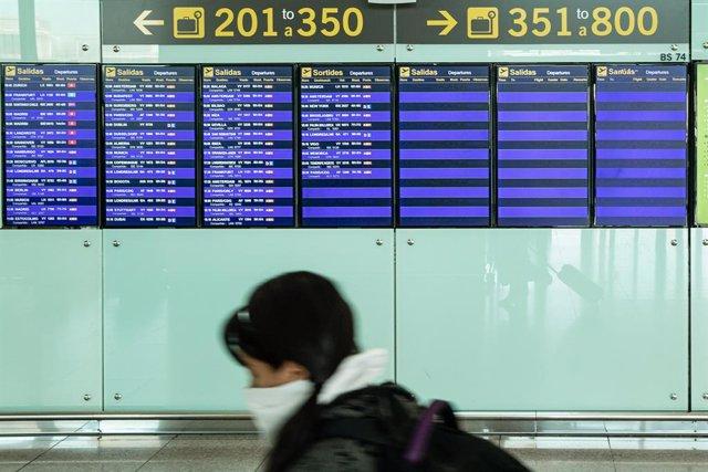 Una passatgera amb mascarilla observa els panells de l'aeroport El Prat de Barcelona durant el sisè dia de confinament després de la declaració de l'estat d'alarma per la pandèmia de coronavirus, a Barcelona / Catalunya (Espanya), a 20 de març de 2020.