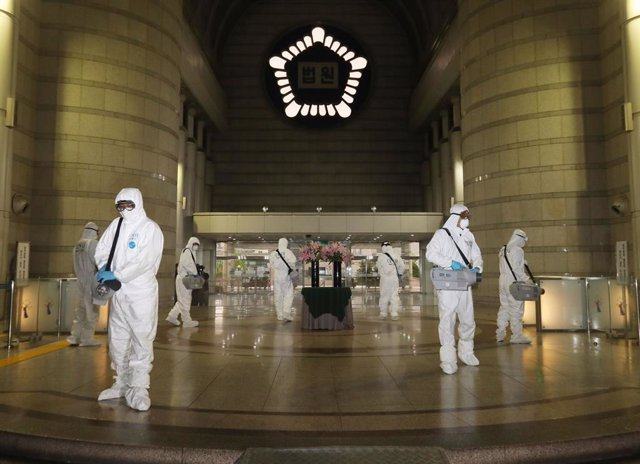 15 May 2020, South Korea, Seoul: Sanitary workers wearing protective suits disinfect the Seoul Central District Court.