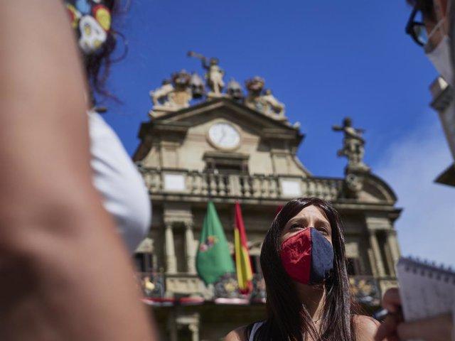 Una jove amb mascarilla a la Plaça del Consistori al moment en el qual de celebrar-se els Sanfermines 2020 hagués tingut lloc el famós chupinazo, a Pamplona, Navarra (Espanya), a 5 de juliol de 2020. Pamplona afronta aquest dilluns amb mesures per int