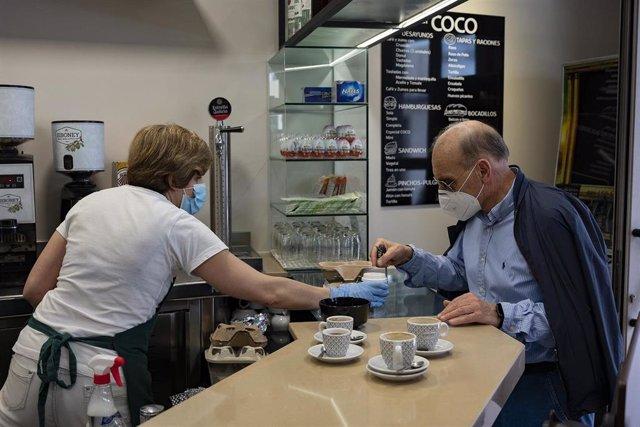 Un hombre toma un café en un bar de la capital de A Coruña, el día que en el que la provincia pasa junto al resto de las que componen Galicia -Pontevedra, A Coruña y Ourense- a la Fase 1 del Plan de Desescalada establecido por el Gobierno de España.  En A