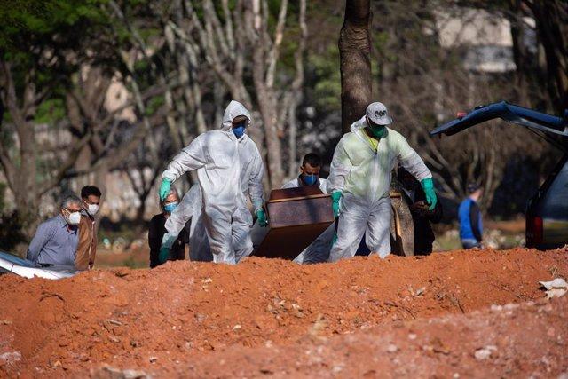 Dos trabajadores del cementerio de Vila Formosa, en Sao Paulo,  trasladan el féretro de una víctima de COVID-19.
