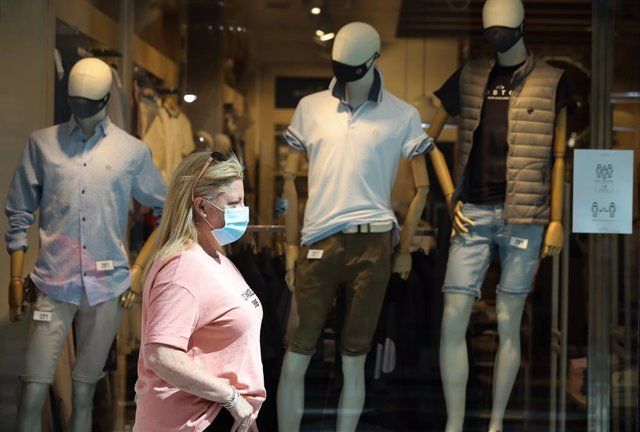 Una dona passa al costat d'una botiga de roba del Centre Plaza Nord 2, La Cúpula de Madrid, a Sant Sebastià dels Reis, Madrid (Espanya), a 9 de juny de 2020.