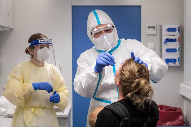 13 August 2020, Baden-Wuerttemberg, Stuttgart: A travel (R) who has been in Switzerland gets tested by medic at a coronavirus testing center set to allow travellers returning from risk areas to take COVID-19 tests at the main railway station in Stuttgart