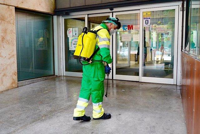 Un operario del Ayuntamiento de Móstoles realiza labores de desinfección a las puertas de un centro sanitario.