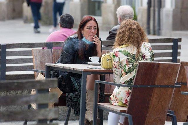 Una persona fuma en una terrassa durant el primer dia de la prohibició de fer-ho en la via pública a Galícia si no existeix una distància de dos metres de separació amb altres persones per evitar contagis de Covid-19, a Lugo ,a 13 d'agost de 2020.