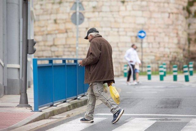 Una persona fuma durante el primer día de la prohibición de realizarlo en la vía pública en Galicia si no existe una distancia de dos metros de separación con otras personas para evitar contagios de Covid-19, en Lugo, a 13 de agosto de 2020.