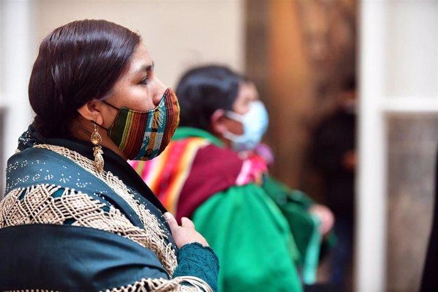 Dos mujeres haciendo uso de la mascarilla durante un acto de celebración por la independencia de Bolivia.