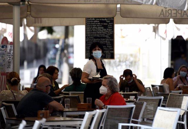 Una camarera con mascarilla atiende a los clientes en una terraza de un bar.