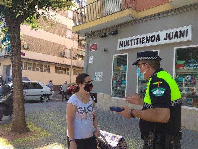 Un policía local de Córdoba habla con una ciudadana sobre el uso obligatorio de la mascarilla.