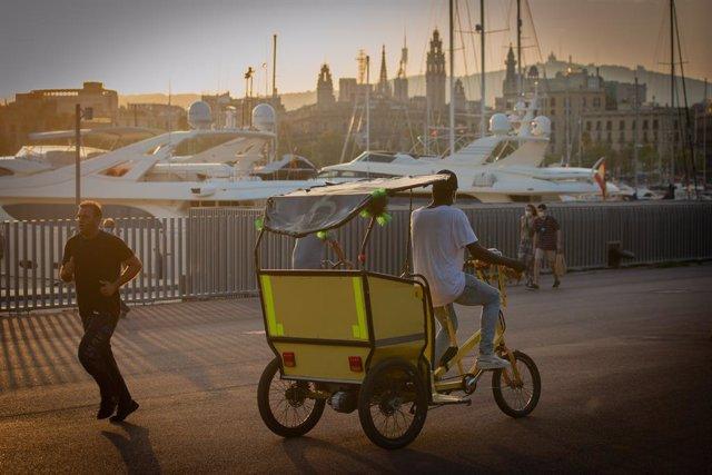 Un home munta en una bicicleta-taxi per Barcelona, Catalunya (Espanya), a 28 de juliol de 2020.