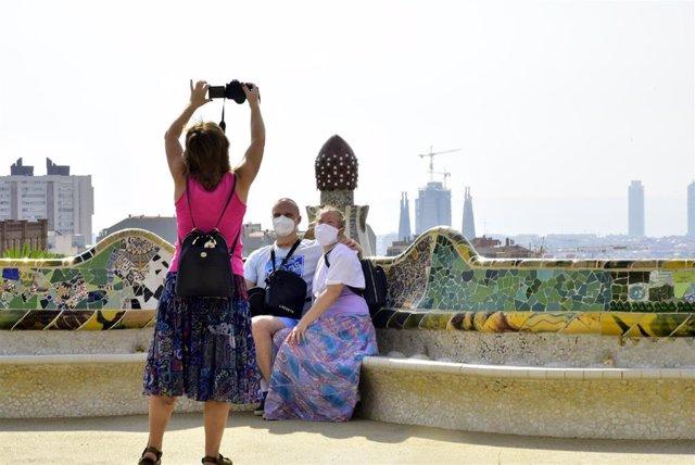 Turistas en la plaza de la Natura del Park Güell de Barcelona, después de que hayan rehabilitado el banco