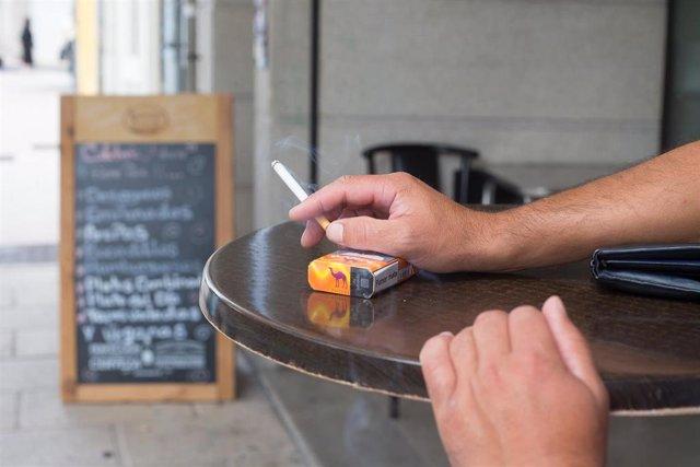 Una persona fuma en una terraza durante el primer día de la prohibición de realizarlo en la vía pública en Galicia si no existe una distancia de dos metros de separación con otras personas para evitar contagios de Covid-19, en Lugo, a 13 de agosto