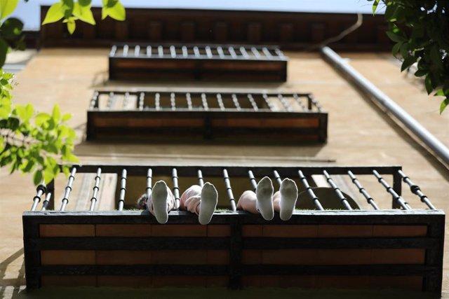 Los pies de unos niños se asoman por su balcón durante el día 53 del estado de alarma por la crisis del Covid-19. En Madrid, (España), a 6 de mayo de 2020