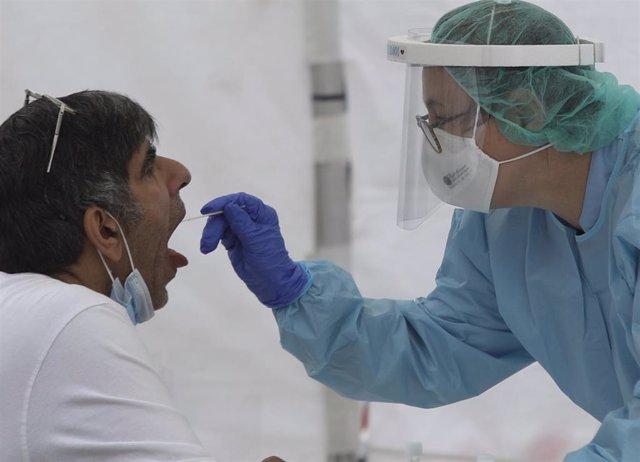 Una sanitaria le realiza un frotis bucal a un paciente.