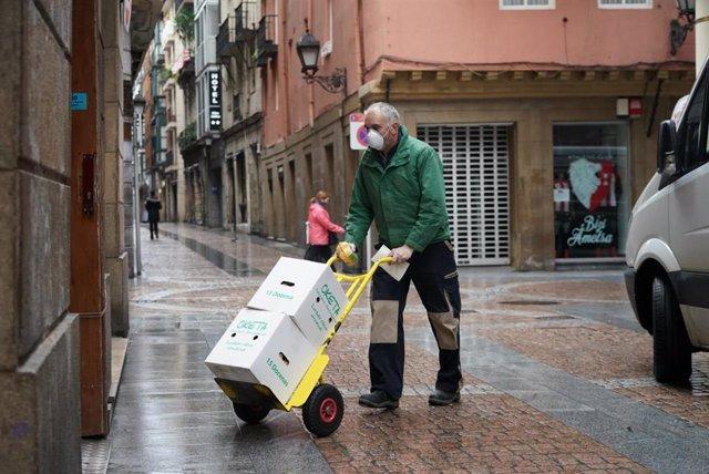 Un hombre con mascarilla carga con material en el caso viejo de Bilbao en el segundo día laborable en estado de alarma en Bilbao, Vizcaya, País Vasco (España), a 17 de marzo de 2020.