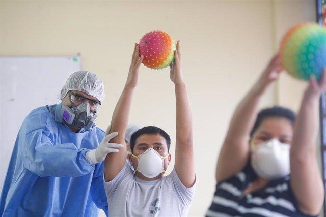 Un trabajador sanitario trabajando en una clínica de rehabilitación con un traje protector por el coronavirus.