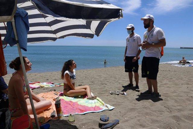 Una pareja de auxiliares de la playa de Andalucía asesoran a bañistas sobre las medidas preventivas sobre el COVID-19 en la playa de La Malagueta. Málaga a 16 de junio del 2020