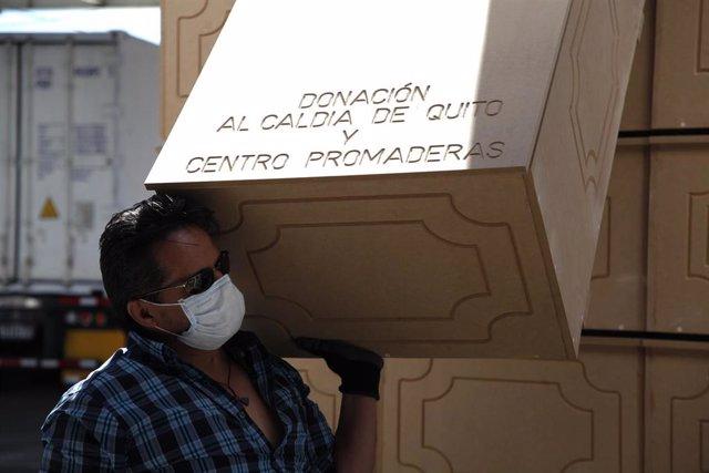 Un hombre carga con uno de los ataudes fabricados de urgencia para hacer frente a la alta demanda que se ha producido en Ecuador en medio de la crisis sanitaria provocada por la COVID-19.