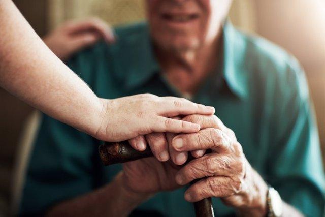 Anciano y cuidadora, dependencia. Bastón, perosona mayor.