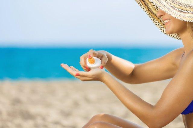 Mujer con crema solar en la playa.