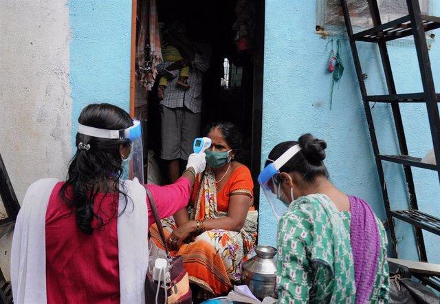 Una trabajadora sanitaria realizanto test puerta por puerta en Bombay, India