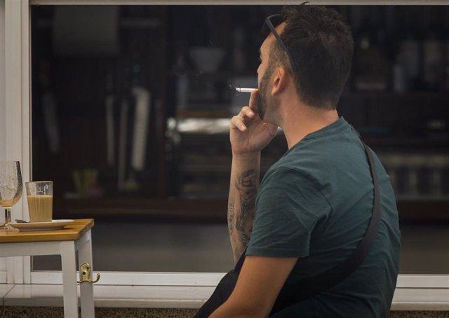 Una persona fuma en una terraza durante el primer día de la prohibición de realizarlo en la vía pública en Andalucía. En Sevilla, (Andalucía, España), a 17 de agosto de 2020.