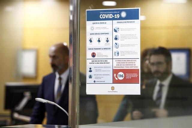 Un cartel en el edificio del Gobierno de Andorra con información básica de la Covid-19 y los ministros de Salud, Joan Martínez Benazet, y Portavoz, Eric Jover, al fondo