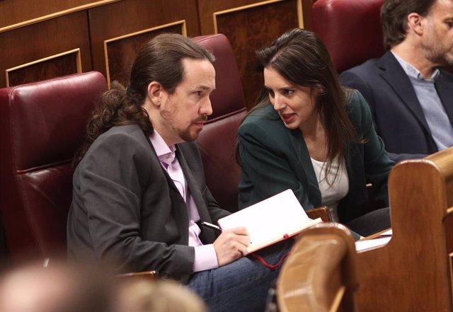 El secretario general de Podemos, Pablo Iglesias, y la portavoz parlamentaria de Unidas Podemos, Irene Montero, hablan en sus escaños en el Congreso de los Diputados durante la primera sesión del debate de investidura del candidato socialista a la Preside