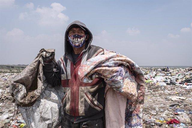Un recolector de basura ataviado con una mascarilla mientras trabaja en uno de los grandes vertederos de Ciudad de México.