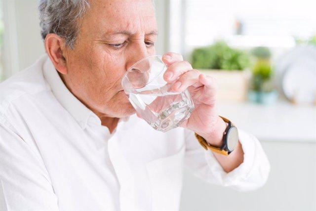Hombre mayor bebiendo un vaso de agua.