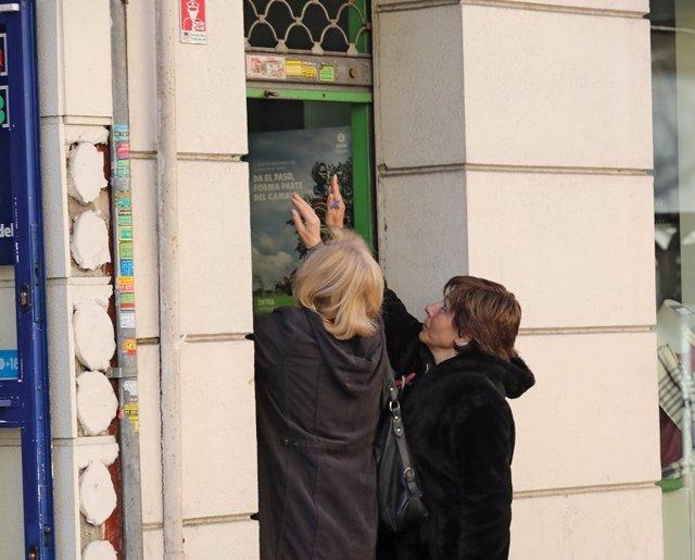 Dues dones tanquen la persiana del seu negoci