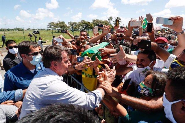 El presidente de Brasil, Jair Bolsonaro, saludando a un grupo de seguidores.