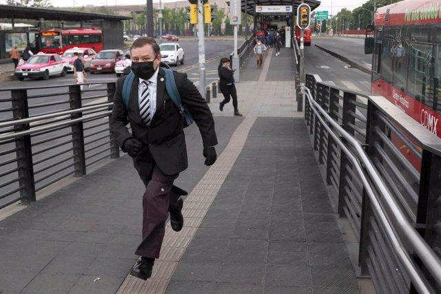 Un hombre con mascarilla se apresura por las calles de Ciudad de  México para no perder el autobus.