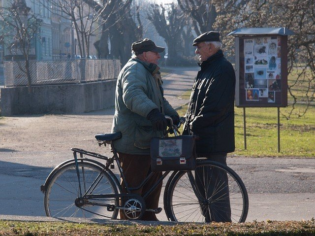 Dos hombres mayores hablando en la calle.