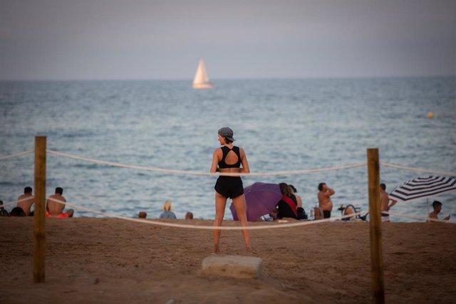 Una banyistes, d'esquena a la càmera, a la platja a Barcelona, Catalunya (Espanya), a 28 de juliol de 2020.