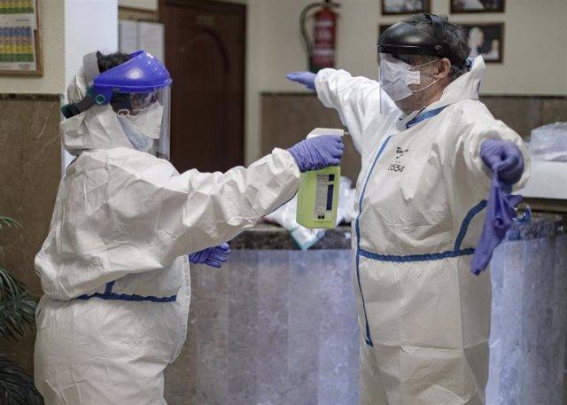 Desinfectan a un trabajador de una residencia.