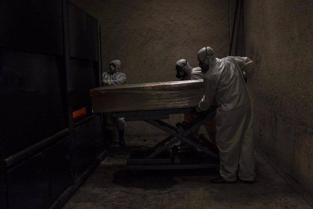 Un grupo de sepultureros acarrea con el ataúd de una víctima de coronavirus una vez ha finalizado el acto religioso en su memoria.