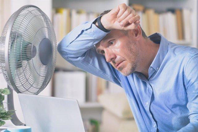 Hombre sudando delante del ventilador.