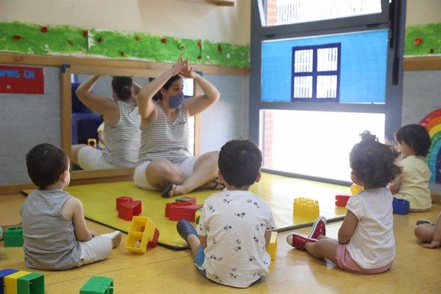 Una docente imparte clases a varios alumnos en la Escuela Infantil  El Tren de la Fresa, el día de su reapertura tras el parón por el coronavirus