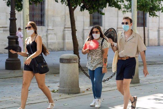 Tres jóvenes pasean con mascarillas y  abanico en el primer día  de uso obligatorio de mascarillas en Sevilla a 15 de julio del 2020