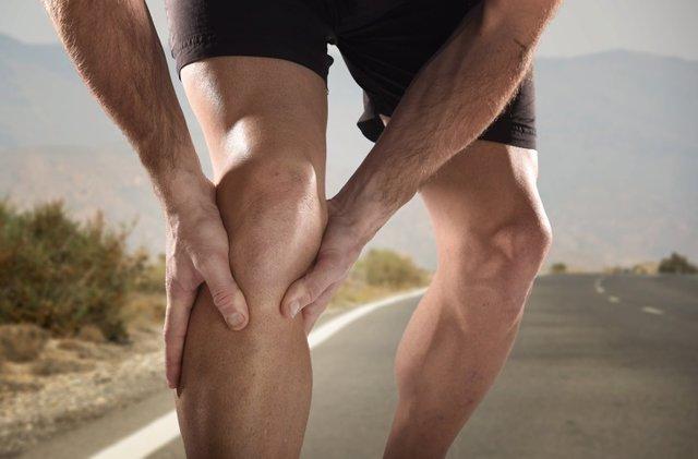 Joven deportista sosteniendo la rodilla, dolor por lesión muscular.
