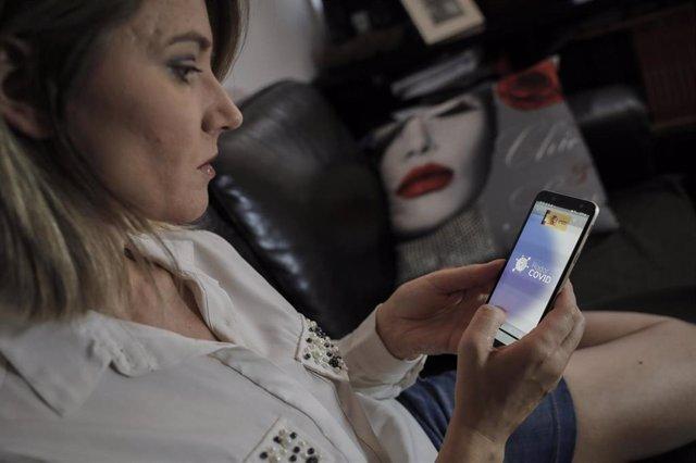 La actriz Nicoleta Hacman hace uso desde su teléfono móvil de la aplicación móvil que desarrolla el Gobierno de rastreo 'Radar COVID', disponible para detectar contactos de positivos de COVID-19. En Madrid, (España), a 12 de agosto de 2020.