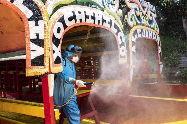 Un trabajador con traje protector desinfecta las coloridas embarcaciones de Xochimilco, en Ciudad de México, mientras el popular lugar turístico se prepara para reabrir este sábado.
