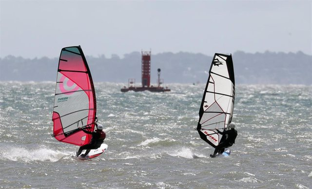 27 June 2020, England, Hampshire: People windsurf over the water in the sea off Calshot beach. Photo: Andrew Matthews/PA Wire/dpa
