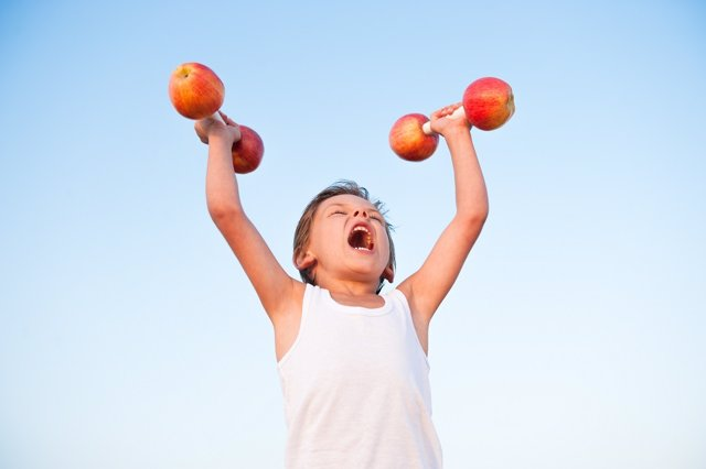 Niño sano haciendo deporte con pesas