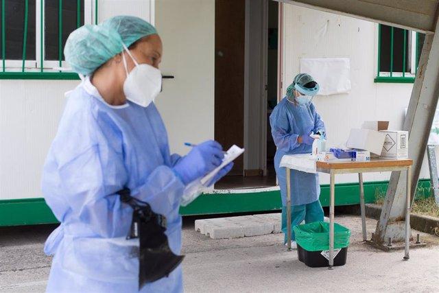 Dos sanitarias preparan pruebas PCR (Archivo)