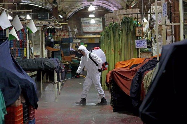 Un trabajador sanitario desinfecta el mercado de La Merced en México.